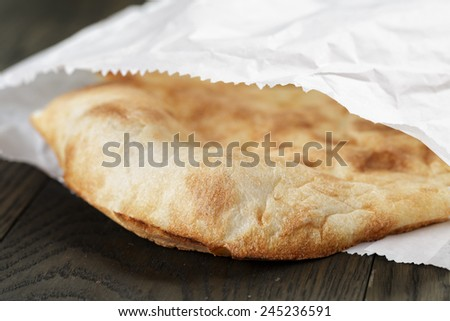 close up of freshly baked flat bread in paper bag - stock photo