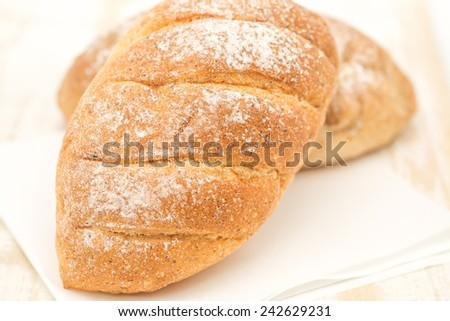 Close up of freshly baked loft of bread for healthy breakfast diet put on painted wood on white background - stock photo