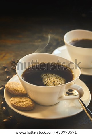 Close up of freshly brewed black coffee by beans and two delicious cookies all placed on a rustic table - stock photo