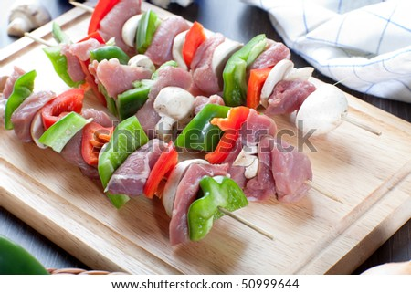 Close up of freshly made meat sticks on wooden board - stock photo