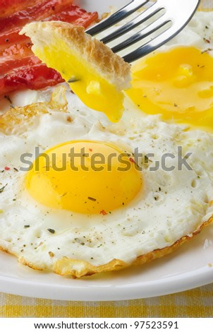 close-up of fried egg and bacon on a plate - stock photo