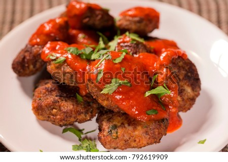 Close up of fried meatballs made from pork and beef meat with tomato sauce and herbs on plate