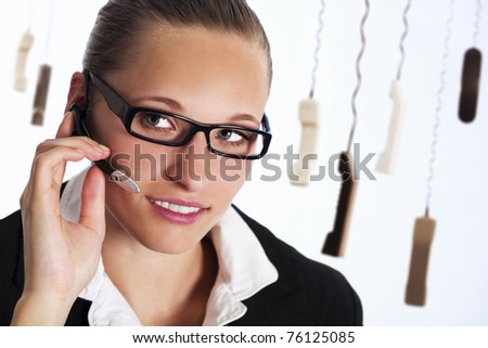 Close up of friendly female phone operator in call centre talking with headset to provide customer service, with many phone receivers hanging in background. - stock photo