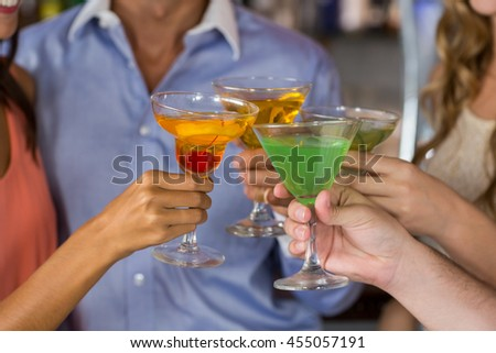 Close-up of friends toasting martini and cocktail glass in bar