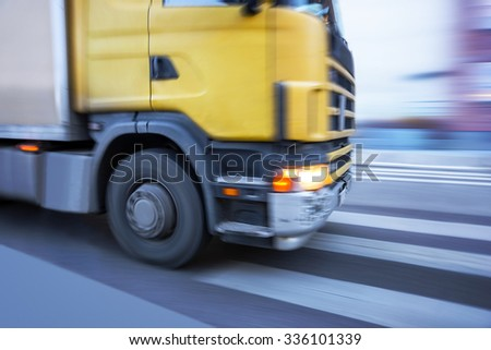 Close up of front of yellow truck on street with pedestrian crossing - stock photo