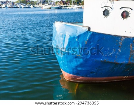 Close up of front side of fisherman ship moored in port. Colorful abstract background of piece of ship - stock photo