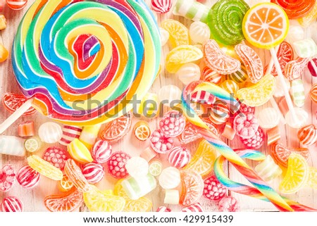 Close up of fruit flavored confections pile on table besides extra large swirl colored sucker and smaller lollipops - stock photo