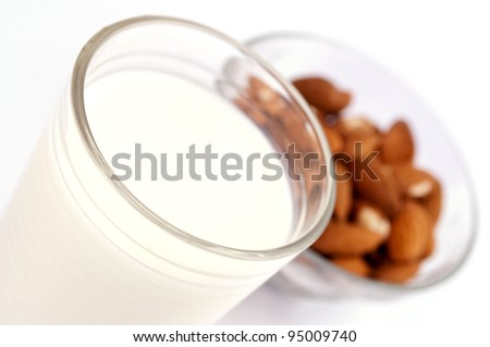 Close-up of full glass of milk and almonds in the bowl - stock photo