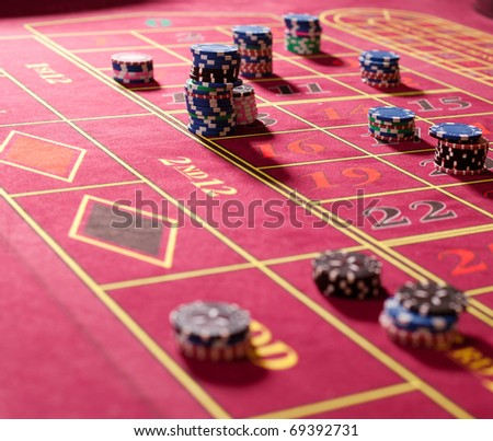 Close  up of gambling chips on red roulette table - stock photo