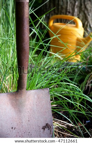Close up of garden shovel with wateing can in the background - stock photo
