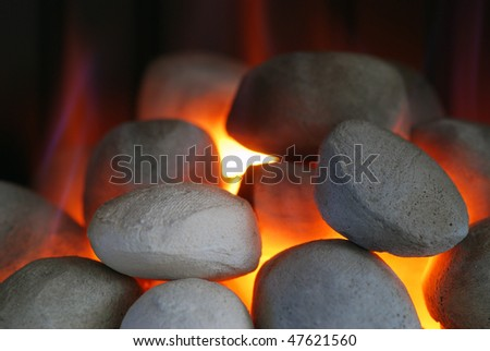 Close up of gas fire showing flames licking stones - stock photo