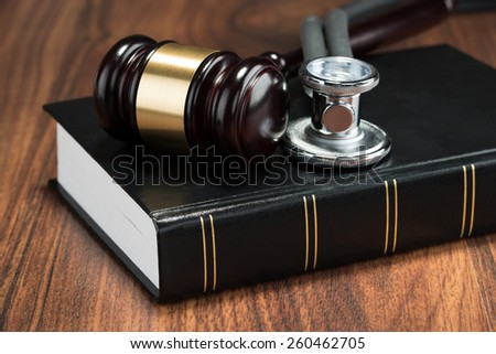 Close-up Of Gavel And Stethoscope On Book Placed On Table - stock photo