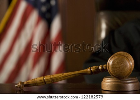 Close up of gavel with American flag in the background in courtroom - stock photo