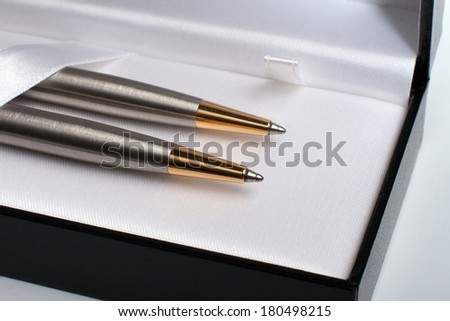 Close up of gift pack of ballpoint pen set made from brushed silver steel with gold in black opened box on white background - stock photo
