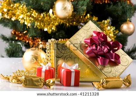 Close-up of giftboxes, sweets and toy ball on background of decorated xmas tree - stock photo