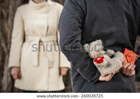 Close-up of gifts young man holding behind his back to surprise his girlfriend - stock photo