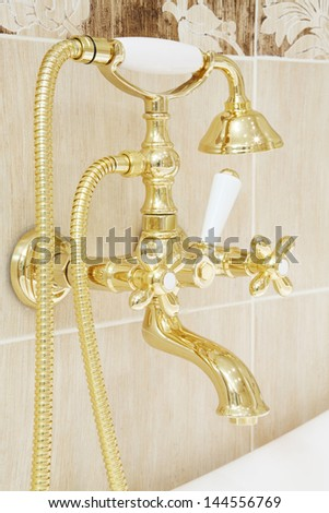 Close-up of gilded faucet with shower heads in light bathroom. - stock photo