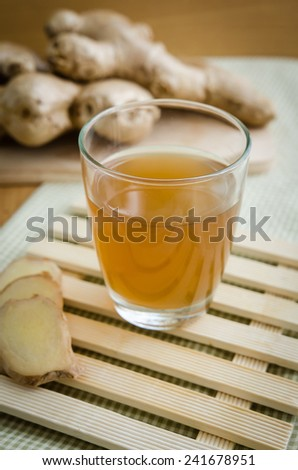 Close up of Ginger tea in glass on bamboo tray - stock photo