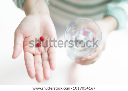 Close Up Of Girl holding Red Pill and glass of water.With Iron of tummy or pregnant. Nutritional Supplements.Sport,pregnancy Concept.Capsules Vitamin And Dietary Supplements.