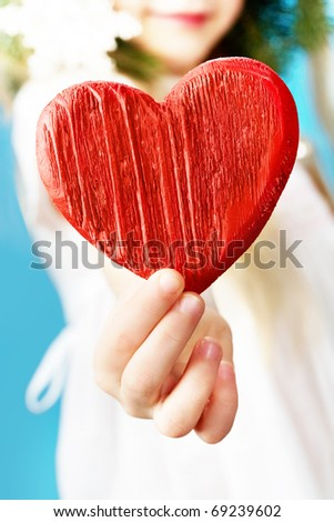 Close-up of girl holding wooden a red heart - stock photo
