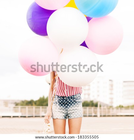close-up of girl in polka-dot short jeans shorts, sleeveless striped top hides in bunch of balloons - stock photo