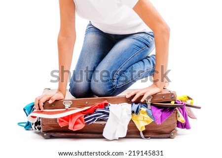 Close-up of girl packing her suitcase - stock photo