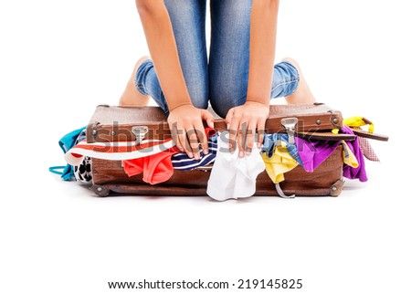 Close-up of girl packing her suitcase full of clothes - stock photo