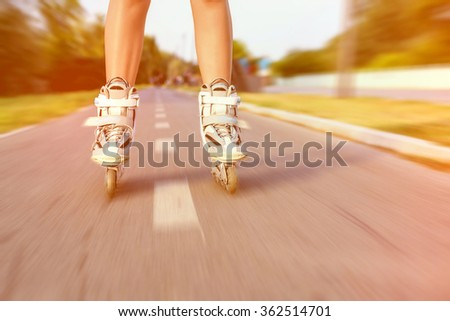 Close up of girl rollerblading in park, motion blur effect and strong colorful tonal photo filter correction.