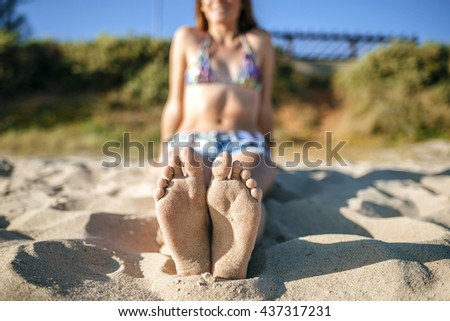Close-up of girl's feet in the beach. Bokeh
