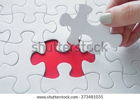 Close up of girl's hand placing the last jigsaw puzzle piece conceptual of problem solving, finding a solution.