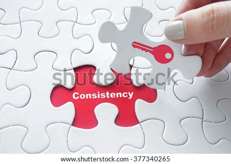 Close up of girl's hand placing the last jigsaw puzzle piece with Consistency is the key concept  - stock photo