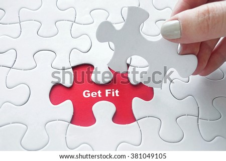 Close up of girl's hand placing the last jigsaw puzzle piece with word Get Fit as Fitness Concept