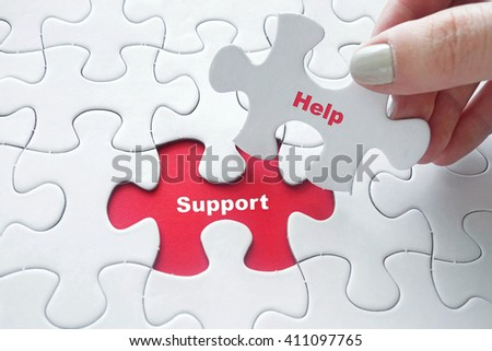 Close up of girl's hand placing the last jigsaw puzzle piece with word Help and Support as business concept - stock photo