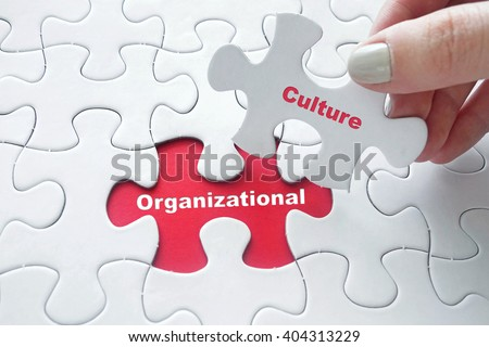 Close up of girl's hand placing the last jigsaw puzzle piece with word Organizational Culture - stock photo