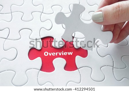 Close up of girl's hand placing the last jigsaw puzzle piece with word Overview - stock photo