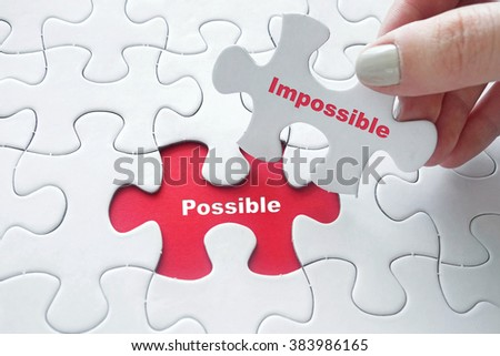 Close up of girl's hand placing the last jigsaw puzzle piece with word Possible and Impossible