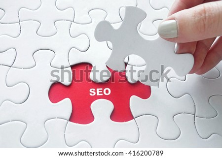 Close up of girl's hand placing the last jigsaw puzzle piece with word SEO - stock photo