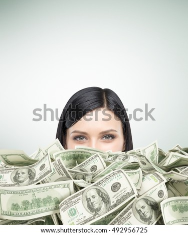 Close up of girl's head with black hair piled up in cash. Concept of being too rich. Mock up
