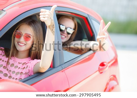 Close up of girls wearing sunglasses in the white car. Little holiday trip of friends - stock photo