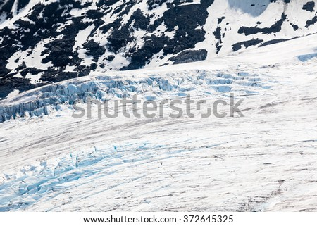 Close up of glacier with blue ice in white snow  - stock photo