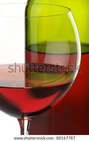 Close-up of glass and bottle of red wine on white background.