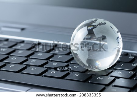 Close up of glass globe on laptop keyboard