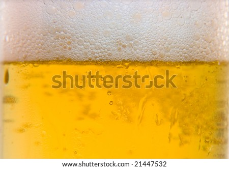 close up of glass of beer with white foam