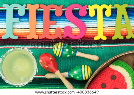 Close up of glass of margarita cocktail garnished with salt rim  on fiesta decorated table. - stock photo