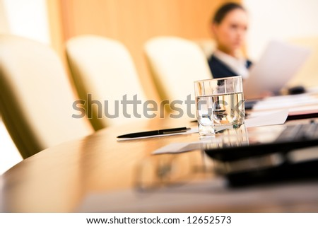 Close-up of glass of water on the background of chairs, papers and working woman