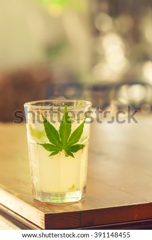 Close-up of glass with ice, alcohol and marijuana leaf on a table as stimulant substance concept - stock photo