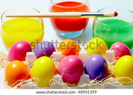 Close-up of glasses with painted water and Easter eggs near by