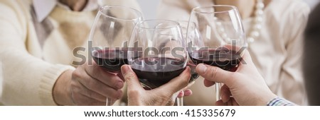 Close-up of glasses with red wine in people's hands. Toasting for holiday