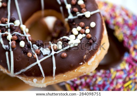 Close up of Glazed Doughnut with chocolate with colourful Donut on the Background. Selective focus. Narrow DOF - stock photo