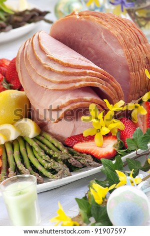 Close up of glazed ham for Easter celebration dinner garnished with asparagus, strawberry, and lemon wedges. - stock photo